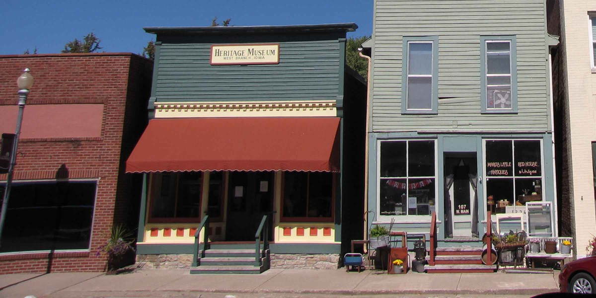 The red awning on green wooden store matches it red and cream trim.