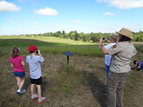 A woman shows children how to take photographs of a grassland.