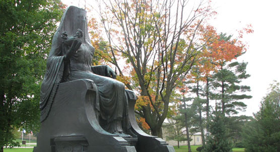 Bronze statue of a seated Egyptian goddess on a marble block with autumn foliage in the background.