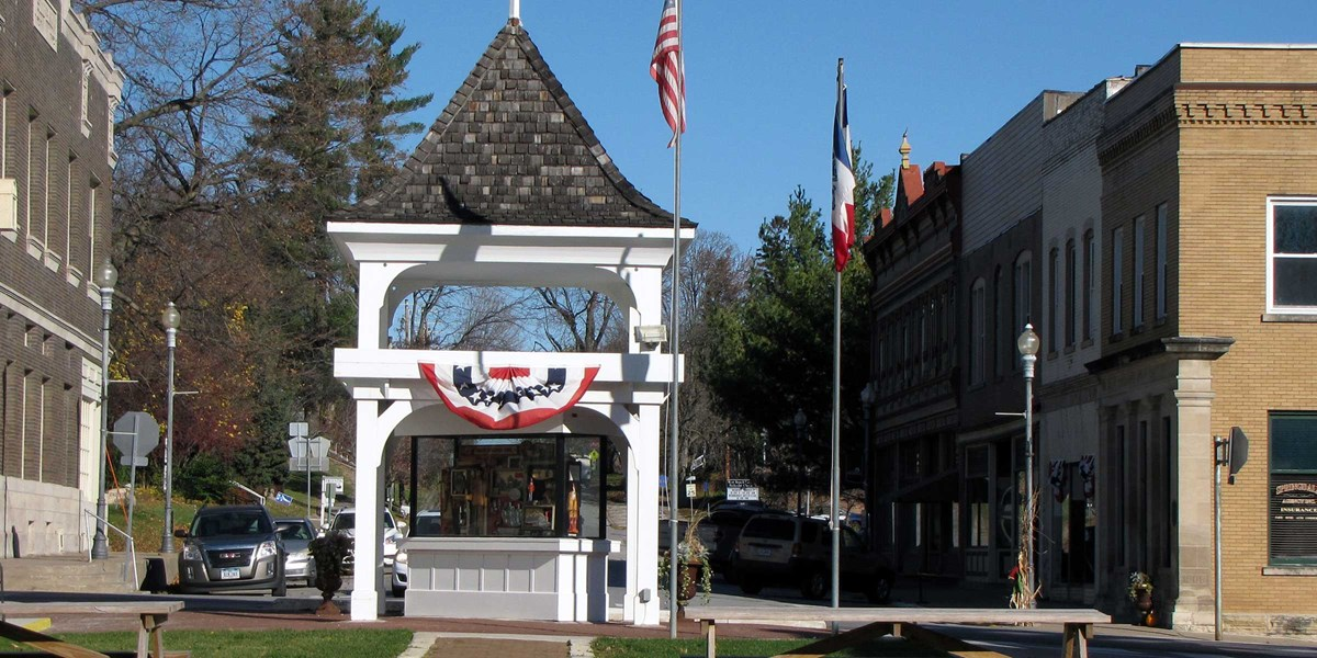 A white gazebo with flags in front of historic commercial downtown block.