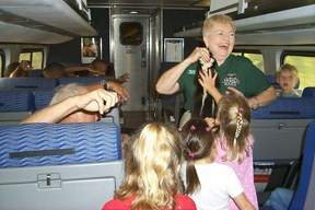 Volunteer for Rails and Trails interacting with kids on the train