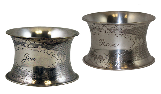 A pair of engraved silver napkin rings given to Joseph P. and Rose F. Kennedy as wedding gifts.