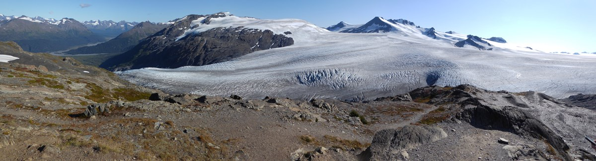 A large field of ice is in the background. In the foreground a path leads to the edge of the icefield
