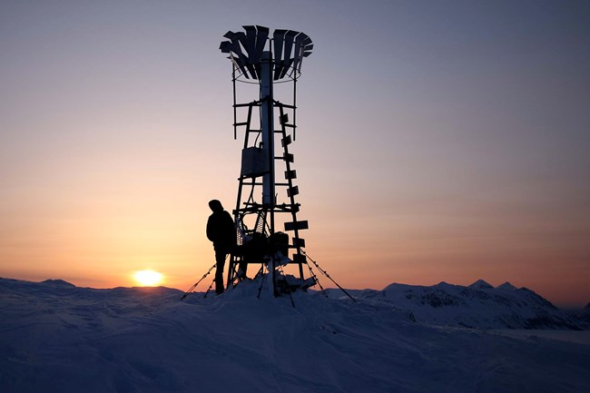 A researcher stands next to a tall weather station on a snow covered field with the sun setting in the background.