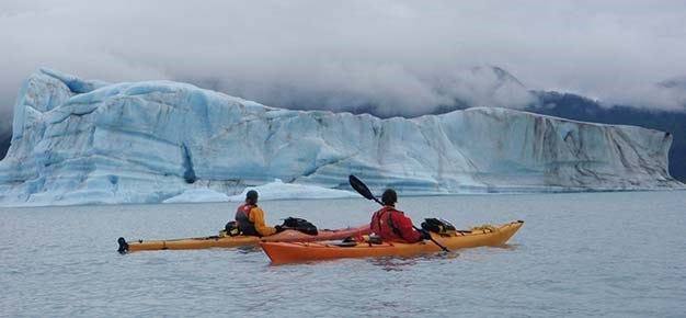 Two kayakers float in the water in front of a giant iceberg.