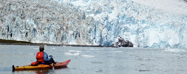 A kayaker pauses in the water near the face of a glacier.