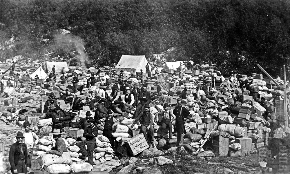 People sit among piles of bags and boxes and tents
