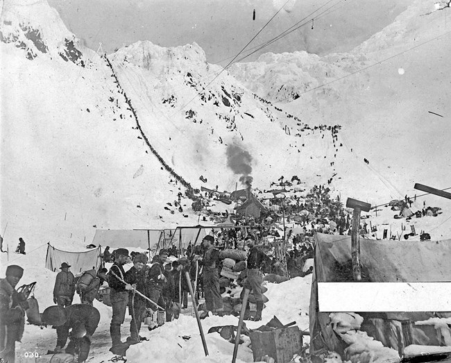 Black and white photo of people with gear standing in front of a snowy mountain pass
