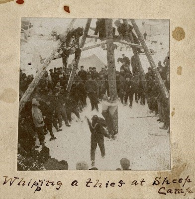 "Black and white photograph of a crowd watching a man tied to a pole.  Text reads ""Whipping a thief at Sheep Camp"""