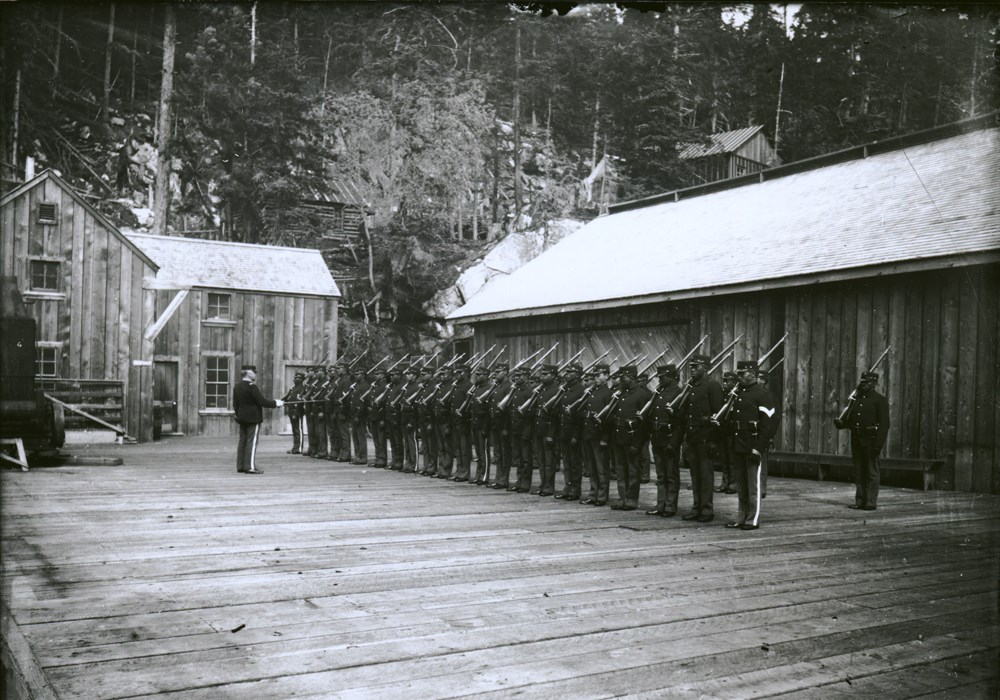 Uniformed soldiers stand in lines on a wooden platform