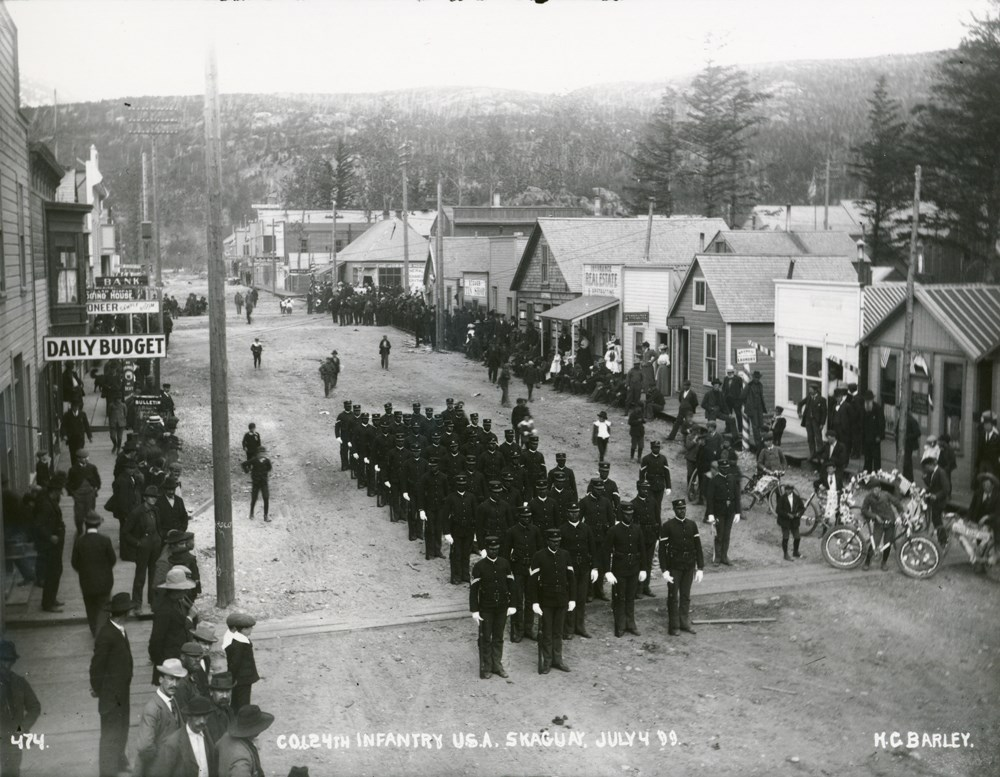 Historic photo of soldiers in a street with people looking on from the sides