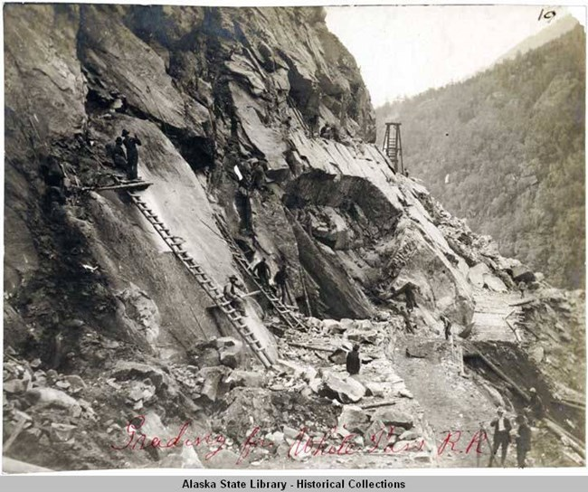 men working to build a railroad on the side of a steep mountain