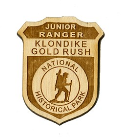 "Wooden badge with text ""Junior Ranger Klondike Gold Rush National Historical Park"""