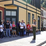 A ranger talks to a group of people next to brightly colored buildings