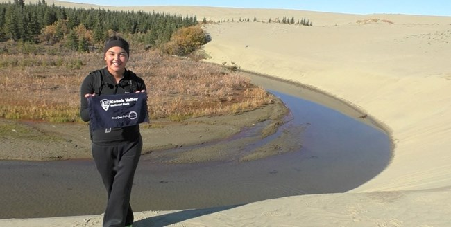 Girl holds park sign up at the Great Kobuk Sand Dunes