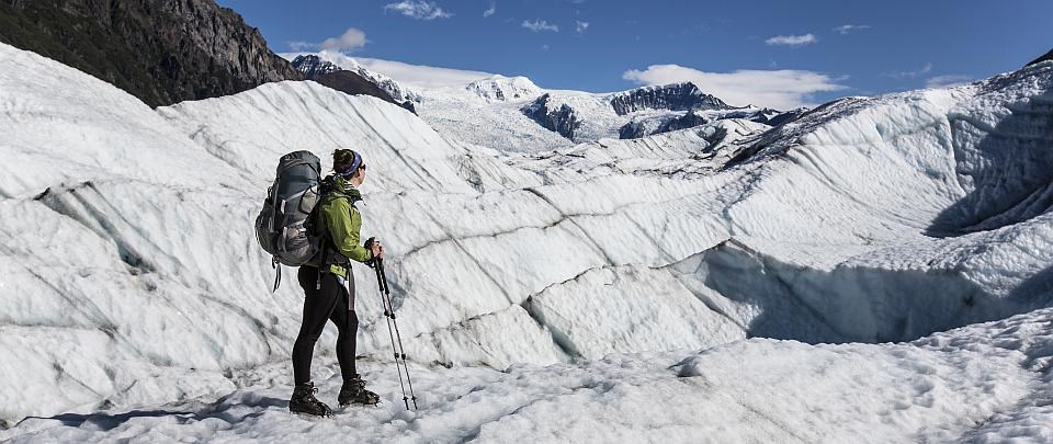 a woman stands with a pack on root glacier