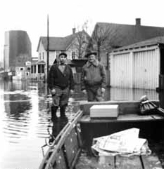 Two men standing in the flooded road.