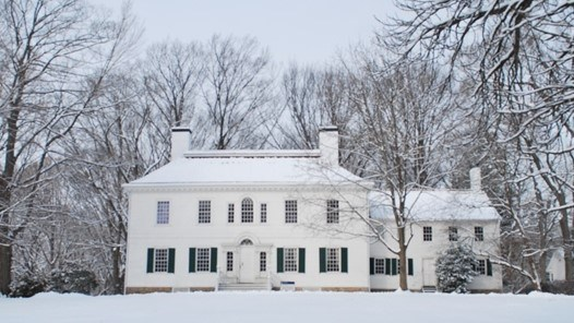 Washington's 1779-1780 Headquarters in winter.  A large white house with a center door surrounded by several trees and snow.