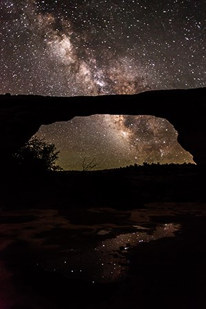 a massive stone arch with the milky way overhead. stars reflect in a pool of water at its base