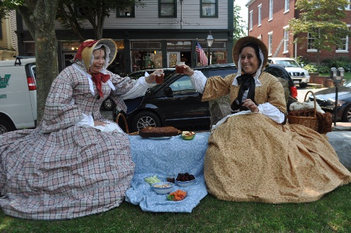 The 1850s ladies, in period dress are seated at a picnic spread with fruits, vegetables and breads.