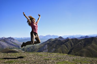 girl in pink shirt jumping on top of a mountain