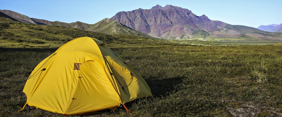 yellow tent on green grass in front on mountains