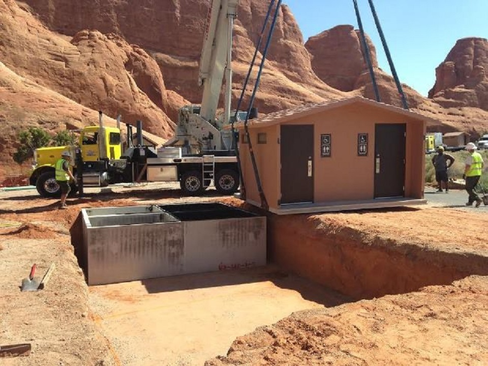 Crane lifting a vault toilet station to move on top of an exposed concrete foundation