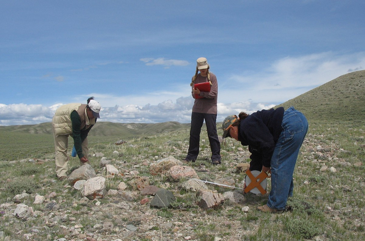 Two students measure a rock pile located in sagebrush and grass covered mountains, while a third student records the data.