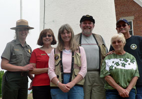 The 2008 Au Sable Lighthouse crew pose in front of the light tower.  Volunteers, Park Rangers, and Eastern National staff work together to make the lighthouse open for visitors.