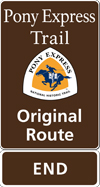A brown tall rectangular highway sign with white text saying: Pony Express Trail Original Route END and a triangular logo with orange and white and a blue pony rider.