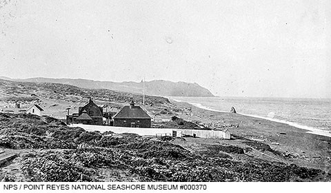 A black and white photo of several wooden structures adjacent to an ocean beach on the right with rugged headlands rising in the distance.