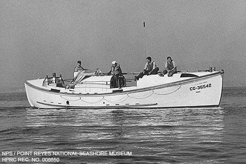 A black and white photo of four lifeboat station crew members aboard a 36-foot-long white lifeboat on gentle water.