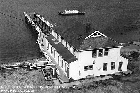 A black and white photograph of a two-story, white-sided building from which a dock extends into a bay. A small barge is anchored near the end of the dock.