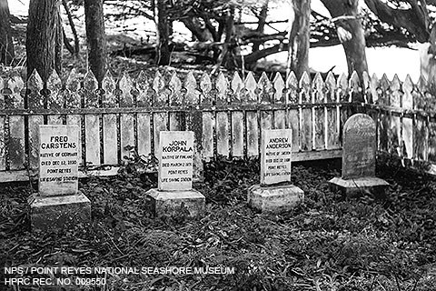 A black and white photo of four grave markers surrounded by a picket fence and trees.