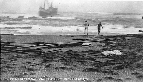 Black and white photo of two men on a beach with a ship caught in heavy surf very close to shore.