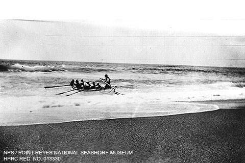 A black and white photo of seven men in a large rowboat rowing away from a beach through moderate surf.