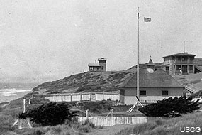 Overview of Point Reyes Naval Radio Compass Station NLG, view to the north. The Point Reyes Life-Saving Station boathouse and flagpole is shown in the foreground. Courtesy of the USCG. On file at Point Reyes National Seashore HPRC#47930.