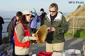Docent holding gray whale baleen talking to a visitor.
