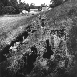 Black and white photo of a woman standing in a surface rupture, where the soil has been turned over, with a barn in the background.