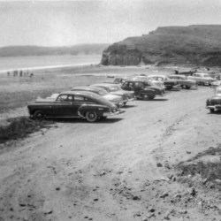 Black and white photo of cars in a parking lot adjacent to the beach.