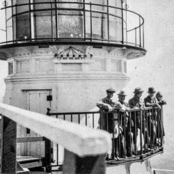 Black and white photo of men standing on lighthouse balcony