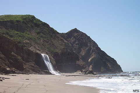 A rocky headland rises over a sandy beach as Pacific Ocean waves wash in from the right. A waterfall, just left of center, cascades over a bluff top onto the beach.
