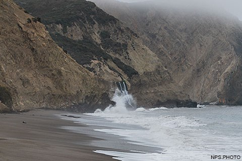 Pacific Ocean waves wash across a sandy beach from the right and crash against the base of a bluff at the center of the image. Just beyond the wave splash, a waterfall cascades on to the beach.