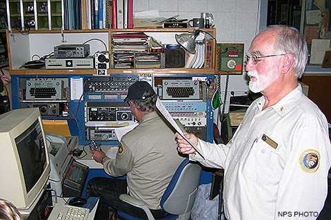 A seated volunteer surrounded by old computers and electronic equipment uses a Morse key to broadcast a Morse code radio message while a volunteer standing on the right reads the message aloud to attendees.