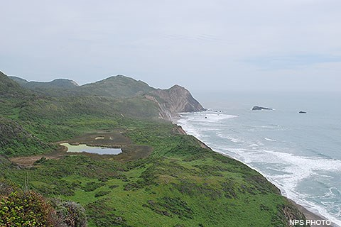 Below overcast skies, Pacific Ocean waves wash in from the right, breaking against a rocky headland in the image's center. Vegetated hills and valleys fill the lower left quadrant of the image, with a small lake filling a depression in the center right.