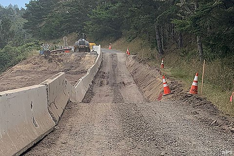 A section of road undergoing road work. Jersey barriers on the left. The road drops abruptly in the foreground.