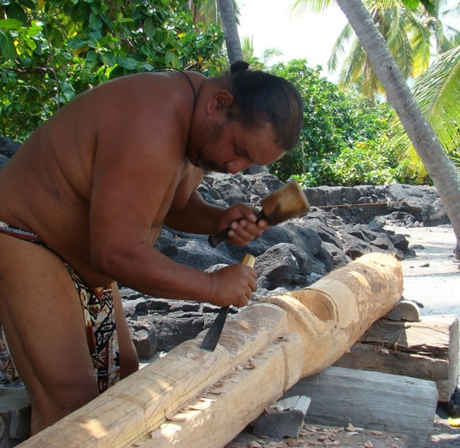 Man in traditional clothing carves a kiʻi image