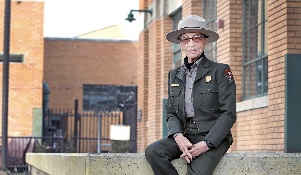 Ranger Betty Soskin sitting in front of the visitor center.