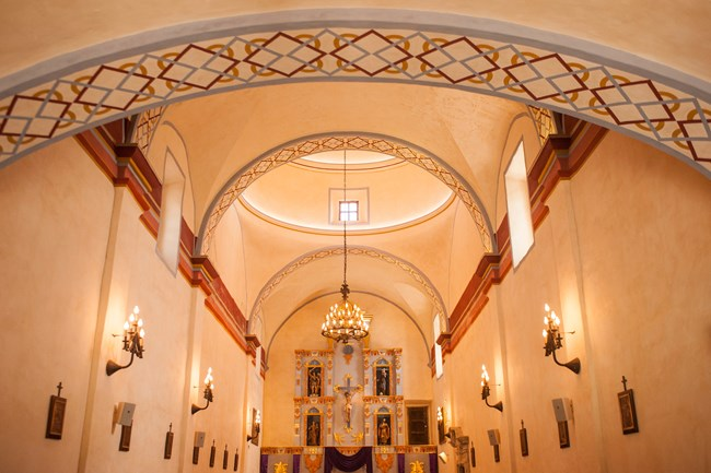 Interior of mission church, looking down pews with light fixtures above.
