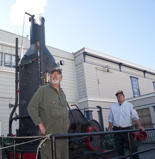 Two men standing next to a steam winch.